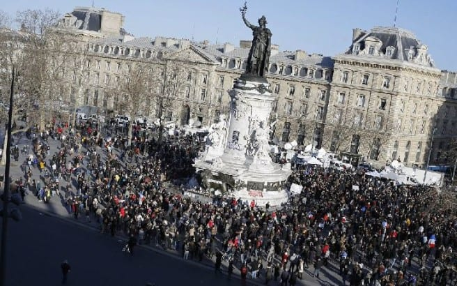 People start gathering at Republique square before the demonstration, in Paris, France, Sunday, Jan. 11, 2015. A rally of defiance and sorrow, protected by an unparalleled level of security, on Sunday will honor the 17 victims of three days of bloodshed in Paris that left France on alert for more violence. (AP Photo/Laurent Cipriani)