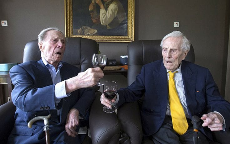 The world's oldest living twin brothers, Paulus (L) and Pieter Langerock from Belgium, 102, toast while sitting in their living room at the Ter Venne care home in Sint-Martens-Latem, Belgium, August 11, 2015. Born on July 8 1913, they never married and until this day sleep side by side in the same room. Eating in moderation, drinking a glass of good wine every day and avoiding chasing women are the secrets of a long life, Belgians Pieter and Paulus Langerock, the world's oldest living twin brothers, say. The brothers have lived together for most of their lives and until this day barely leave each other's side, sharing a room at their nursing home just outside the Belgian town of Ghent. Picture taken August 11, 2015. REUTERS/Yves Herman TPX IMAGES OF THE DAY